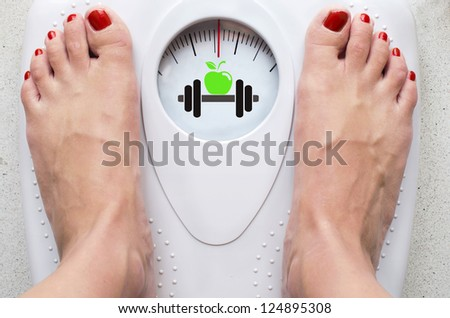 Female feet on bathroom scale with symbols for diet and fitness