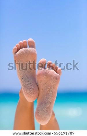 Female feet on blue sky and sea background #656191789