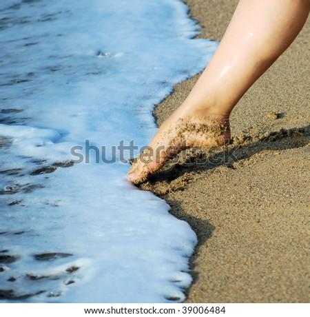 female feet on sand and in sea foam