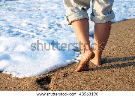 female feet on sand and in sea foam