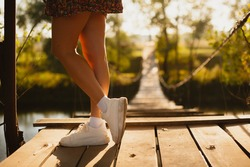 Female feet on the background of a suspension bridge during sunset.