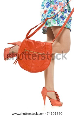 Female feet orange  an orange bag and shoes on a high heel