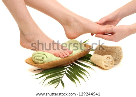 Female feet receiving a massage, isolated on white