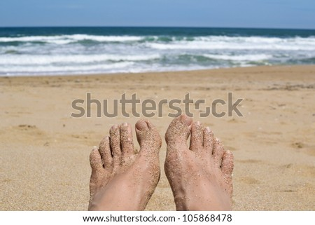 Female feet relaxing on the sandy beach overlooking the blue sea