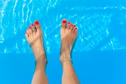 female feet splashing in the swimming pool