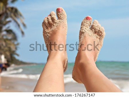 Female feet, stained in the sand, on the background of a sea landscape