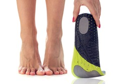 female feet stand on their toes and orthopedic insole in the hand