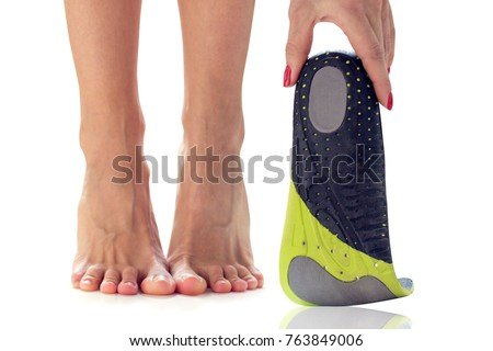 female feet stand on their toes and orthopedic insole in the hand #763849006