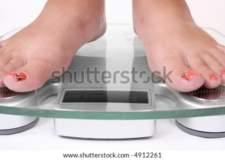 Female feet standing on a bathroom scale