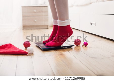 Female feet standing on electronic scales for weight control in red socks with Christmas decoration