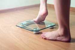 Female feet standing on electronic scales for weight control on wooden background. The concept of slimming and weight loss