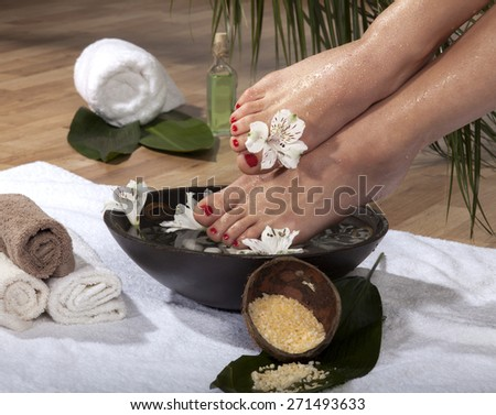 Female feet with drops of water soaked in spa bowl with flowers and rocks.