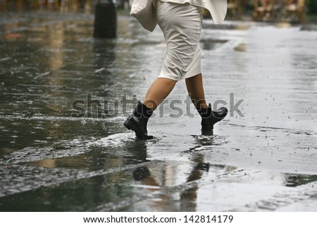female feet with heels shoes walk on water when it rains
