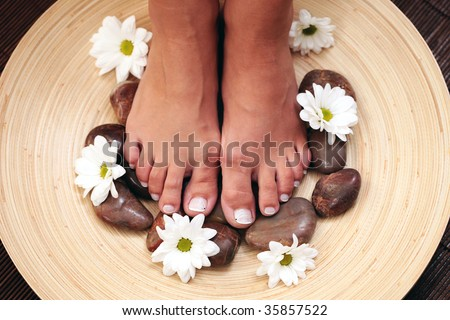 female feet with pebbles and flowers - beauty treatment