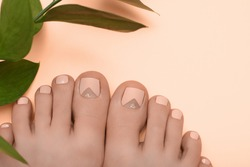 Female feet with pink nail design. Pink nail polish pedicure on pink background