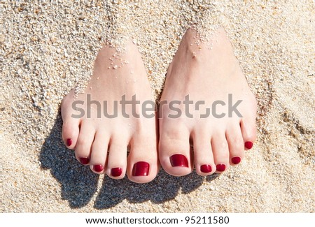 female feet with red pedicure in beach sand