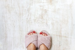 female feet with red toenails in home fur fluffy pink slippers on a light wooden background. flat lay. Top view. The concept of a cozy bright girl house.