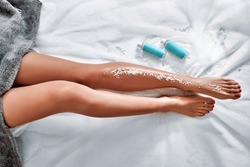 Female feet with sea salt on white towel in salon. Top view