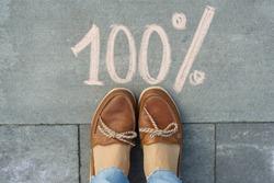 Female feet with text 100 percent written on grey sidewalk.