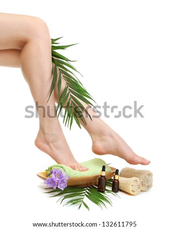 Female feet with towel - spa concept, isolated on white