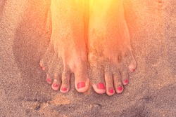 Female feets with pink nails on the sand in the sunlight
