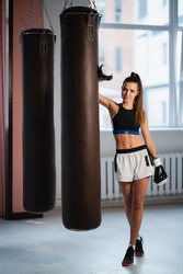 Female fighter trains her punches, training day in the boxing gym, the girl trains a series of punches