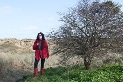 Female figure wearing mask during Covi-19 outbreak lockdown outdoors for beach walk in Autumn 2020 sunny landscape wearing red jacket, boots standing on grass by a bare tree with sand dunes background