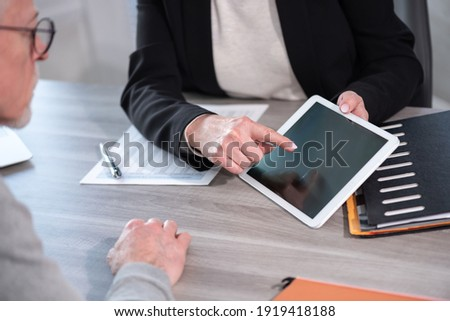 Female financial adviser giving information on digital tablet to her client Photo stock ©