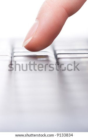 Female finger on the keyboard. Close up.