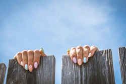 Female fingers on the fence. Isolated female hands