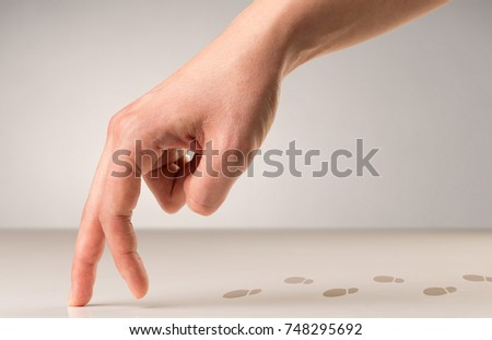 Female fingers walking on white surface with footsteps behind it #748295692