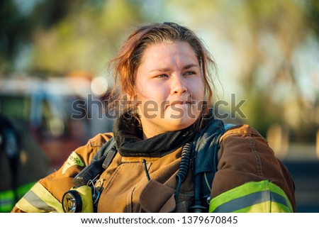 Female firefighter isolated in full bunker gear after a fire.  Stock photo ©
