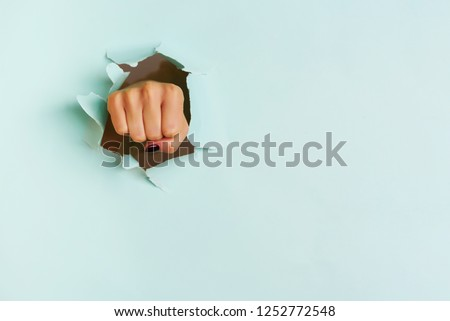 Female fist punching through blue paper background. War, struggle, conflict, feminist concept. Banner with copy space.