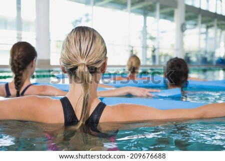 Female fitness class doing aqua aerobics with foam rollers in swimming pool at the leisure centre