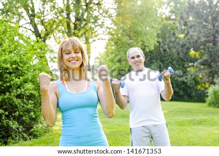 Female fitness instructor exercising with middle aged man in green park