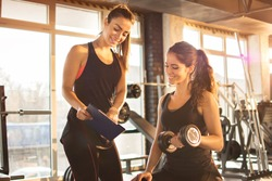 Female fitness instructor showing exercise progress on clipboard to young athletic woman at gym.