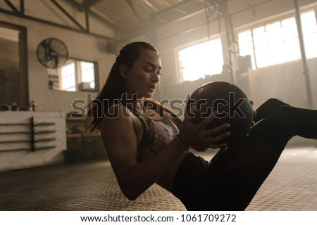 Stock Photo Female fitness model exercising with medicine ball at gym. Young woman doing workout using fitness ball.