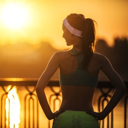 Female fitness model training outside in the city on a quay standing in a sunny bright light on sunrise. Sport lifestyle.