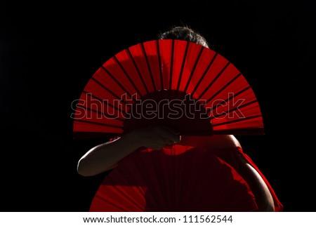 Female flamenco performer hidden behind her folding fans