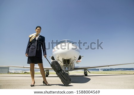 Female flight attendant with suitcase in front of airplane