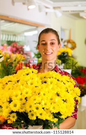 Female florist in flower shop or nursery presenting flowers