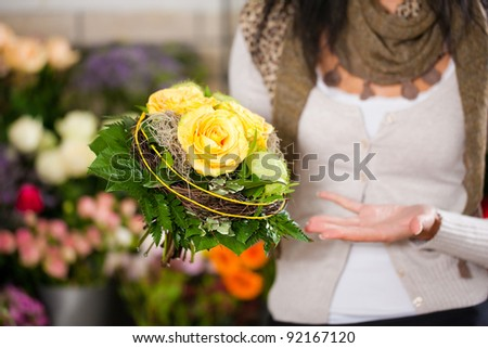 Female florist in flower shop or nursery presenting her plants on display