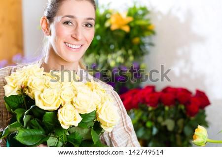 Female florist in flower shop or nursery presenting roses