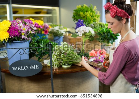 Female florist preparing flower bouquet in flower shop