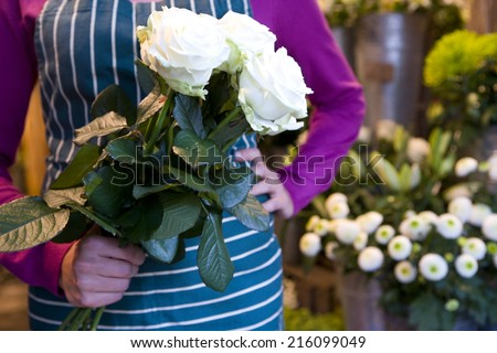 Female florist with bunch of roses, mid section
