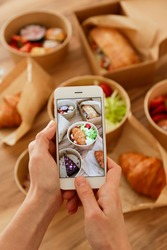 Female food blogger reviewing takeout food, taking video on phone. Italian sub sandwich, french croissant w/ salmon, chocolate cheesecake. Close up, top view, pov, copy space, wooden table background.