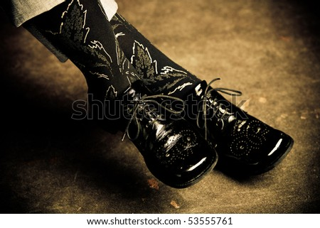 female foot in black shiny shoes and black