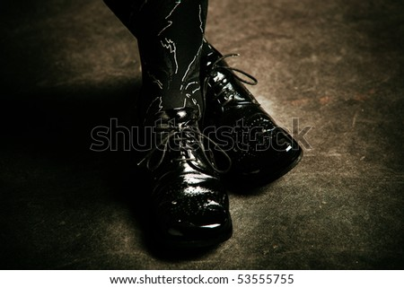 female foot in black shiny shoes studio shot - stock photo