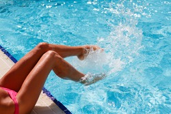 Female foot in blue water. Feet splashing in the pool. Women's legs playing and frolicking with water in a swimming pool.