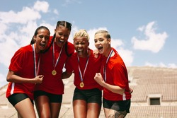 Female football team celebrating the victory at stadium. Woman soccer players with medals shouting in joy after winning the championship.